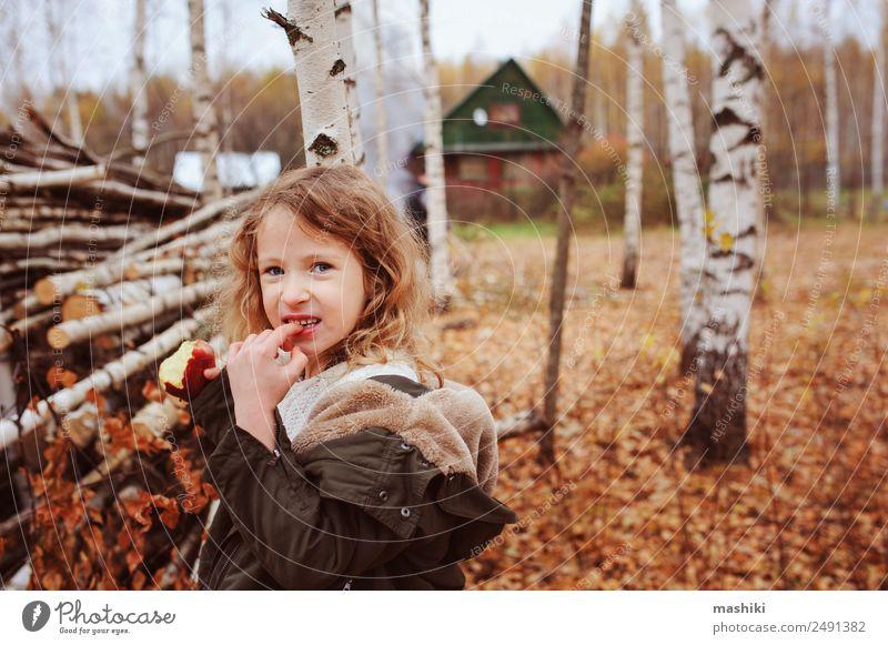 fröhlich lustiges Kind Mädchen isst frischen Apfel im Herbst Frucht Lifestyle Freude Glück Spielen stricken Garten Kindheit Natur Wärme Blatt Wald Schal Lächeln