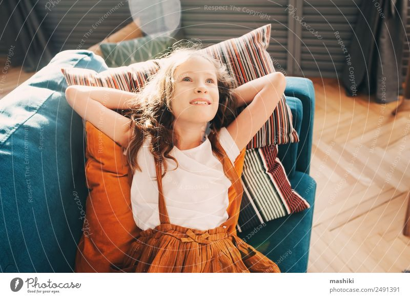 fröhliches Kind Mädchen, das sich auf der gemütlichen Couch im modernen Wohnzimmer entspannt. Lifestyle Glück Wohnung Haus Umzug (Wohnungswechsel)