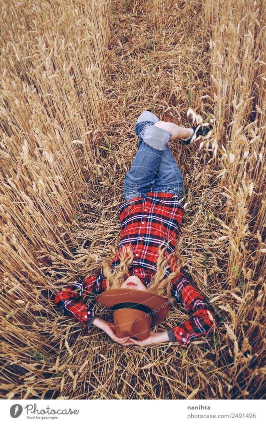 Junge Frau ruht auf einem Weizenfeld. Getreide Bioprodukte Lifestyle Stil Wellness Erholung Freizeit & Hobby Ferien & Urlaub & Reisen Freiheit Sommer