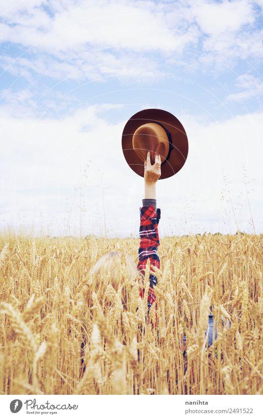 Hand hält einen Cowboyhut in einem Weizenfeld. Getreide Design Freude Freiheit Sommerurlaub Landwirtschaft Forstwirtschaft Arme Umwelt Natur Landschaft Herbst
