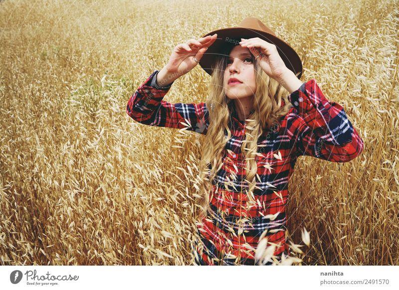Junge Frau, die sich vor der Sonne auf einem Weizenfeld bedeckt. Getreide Lifestyle Stil Freiheit Sommer Sommerurlaub Mensch feminin Jugendliche 1 18-30 Jahre