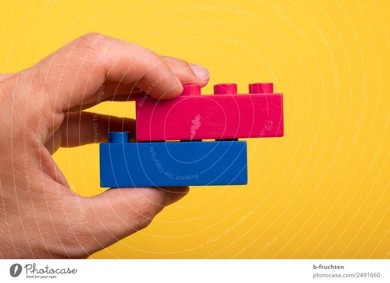 Zwei Bausteine aufeinander Hand Finger Kunststoff festhalten blau gelb Zusammensein Liebe Treue Zufriedenheit Spielzeug versetzt paarweise Paar zusammenpassen