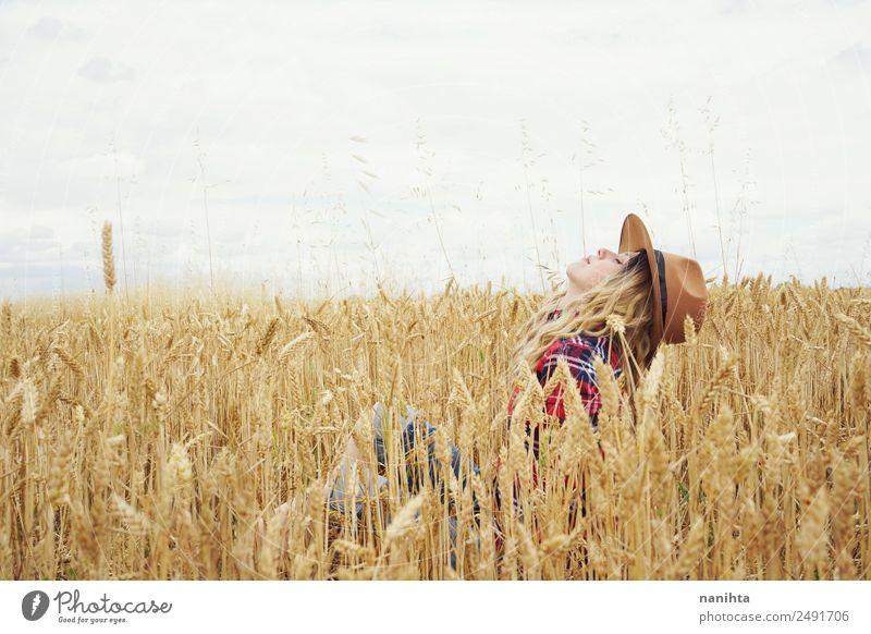 Junge Frau umgeben von Weizenkulturen Getreide Weizenfeld Bioprodukte Lifestyle Stil Freude Wellness harmonisch Wohlgefühl Abenteuer Freiheit Sommer