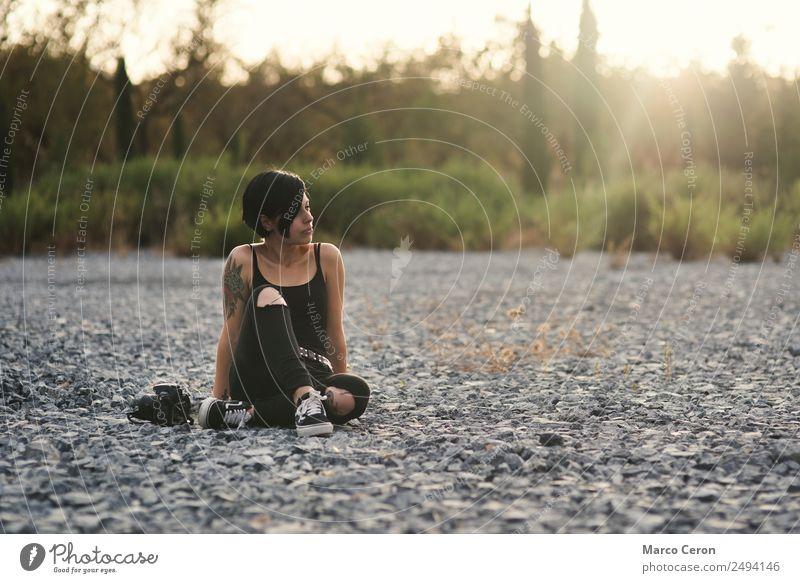 Hübsches Fotografenmädchen in schwarzer Kleidung sitzt mit ihrer Kamera auf dem Steinboden in der Natur attraktiv Hintergrund Hintergrundbeleuchtung schön
