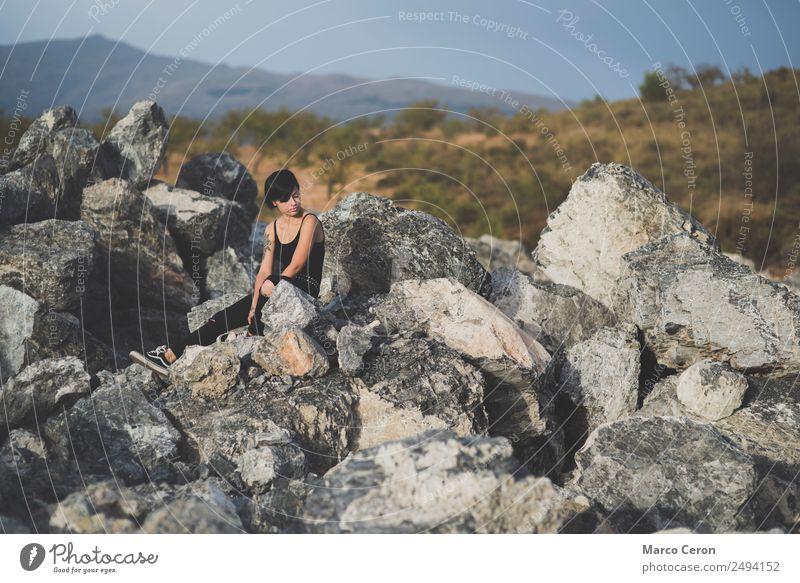 Hübsche junge Frau, die auf dem Land auf den Felsen sitzt und denkt attraktiv Hintergrund schön schwarze Kleidung brünett Fotokamera Kaukasier Landschaft Tag
