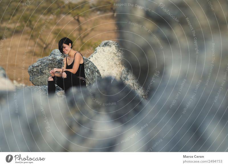 Hübsche junge Frau lächelt und sitzt glücklich auf den Felsen in der freien Natur attraktiv Hintergrund schön schwarze Kleidung brünett Fotokamera Kaukasier