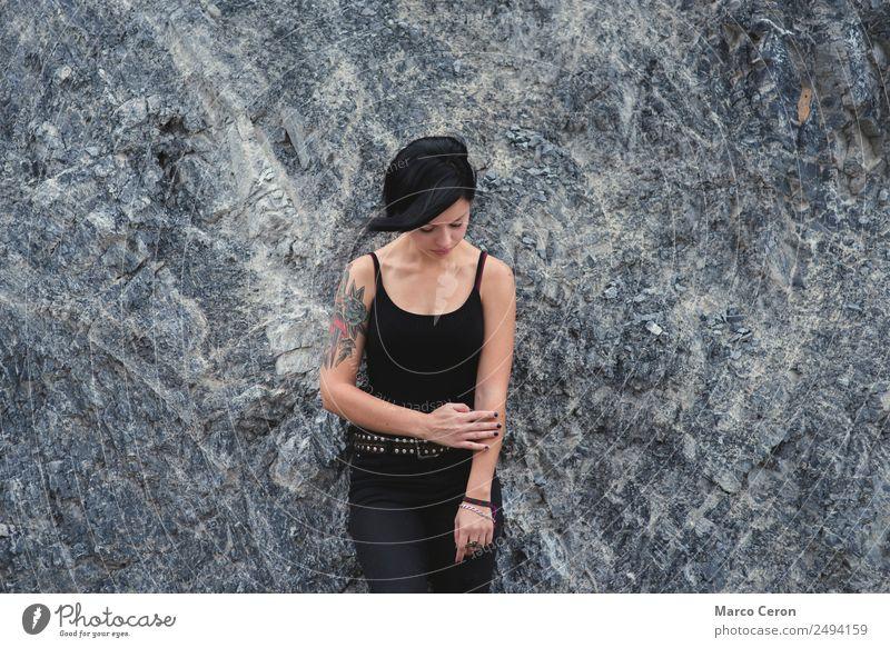 schönes brünettes, kurzhaariges Mädchen, das sich draußen an eine graue Felswand lehnt und schwarze Kleidung trägt attraktiv Hintergrund Schwarzes Haar Atmung