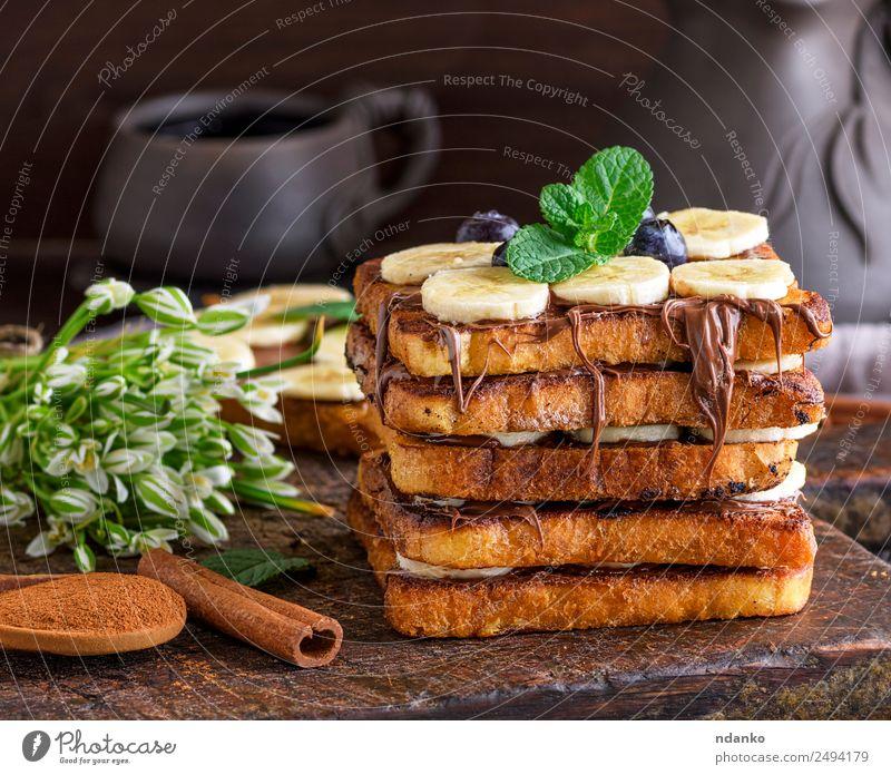 Französischer Toast mit einer Banane Frucht Brot Dessert Ernährung Frühstück Blume Holz Essen frisch lecker braun Tradition Zuprosten Schokolade Hintergrund