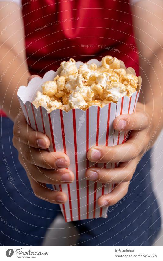 Eine Tüte Popcorn Süßwaren Fastfood Entertainment Junge Hand Finger 3-8 Jahre Kind Kindheit Veranstaltung Fernsehen festhalten frisch süß Popkorn Kino voll