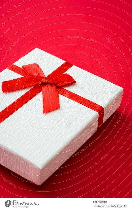 Weiße Geschenkbox auf rotem Hintergrund Feste & Feiern Valentinstag Muttertag Weihnachten & Advent Silvester u. Neujahr Hochzeit Geburtstag Verpackung Paket