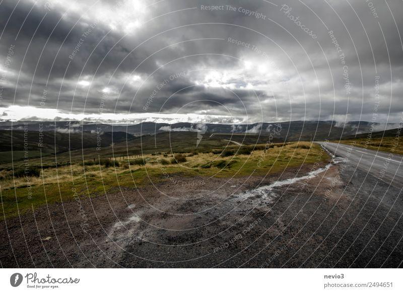Dunkle Wolken über dem schottischen Hochland Landschaft Wiese Feld bedrohlich dreckig kalt nass trist braun grau dunkel dunkle Wolken Hügel Schotterstraße