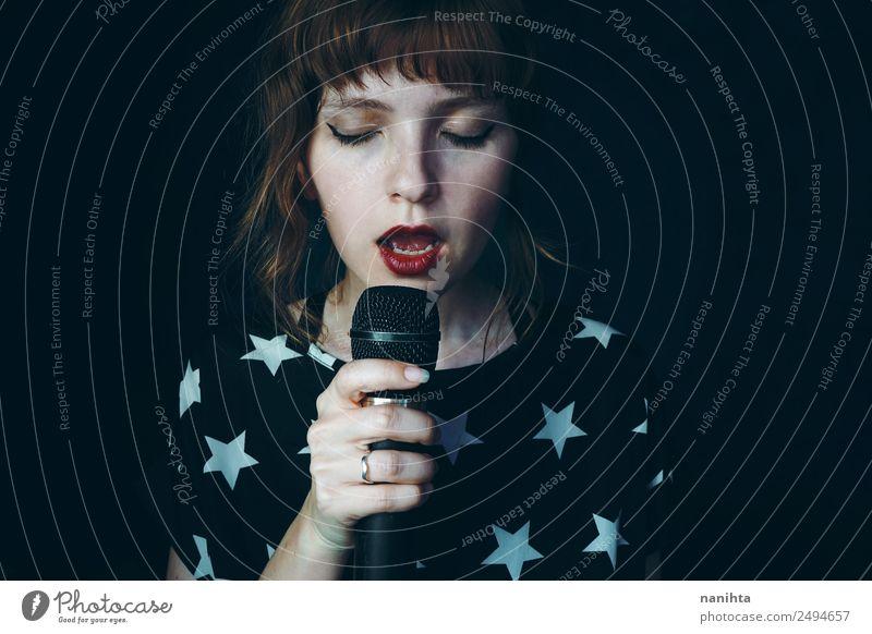 Junge Frau singt in die Dunkelheit. Lifestyle elegant Stil Design Gesicht Freizeit & Hobby Party Veranstaltung Musik Feste & Feiern Technik & Technologie
