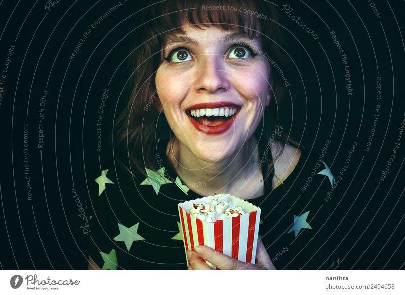 Fröhliche junge Frau beim Anschauen eines Films Lebensmittel Popkorn Lifestyle Stil Wellness Freizeit & Hobby Entertainment ausgehen Mensch feminin Junge Frau