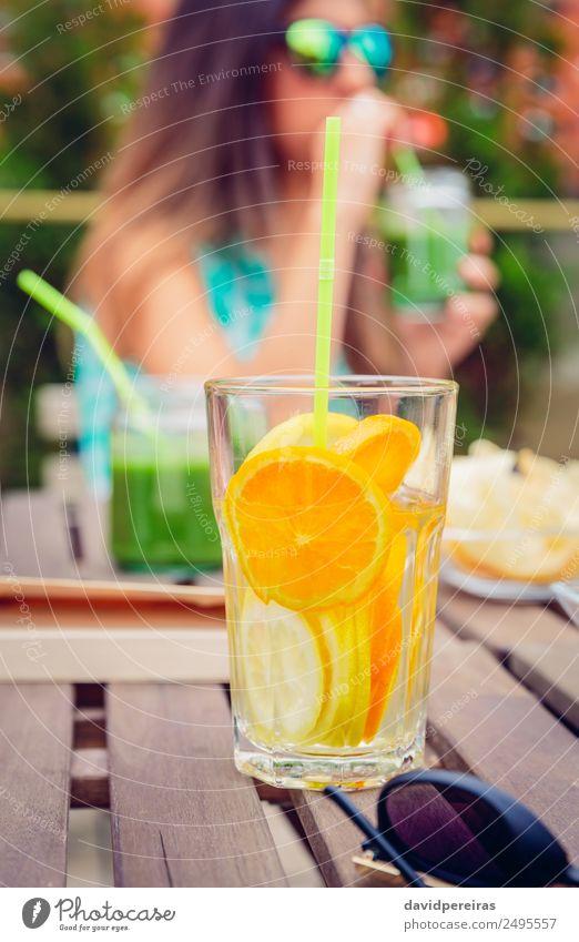 Aufgegossene Fruchtwasser-Cocktails und Frau, die grünen Smoothie trinkt. Gemüse Ernährung Diät Getränk Saft Tee Sommer Tisch Mensch Erwachsene Natur Holz