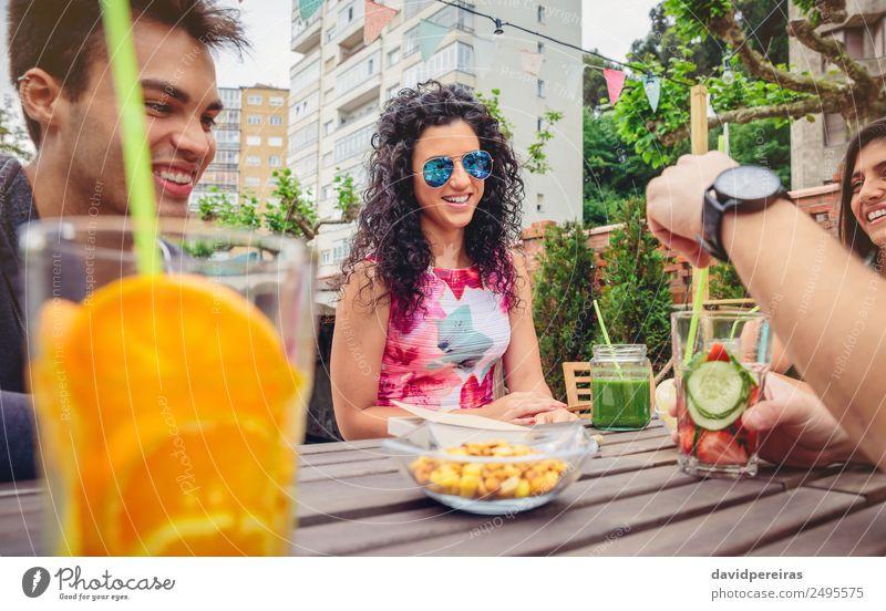 Junge Frau im Gespräch mit Freunden an einem Sommertag Gemüse Frucht Getränk Lifestyle Freude Glück schön Freizeit & Hobby Ferien & Urlaub & Reisen Garten Tisch