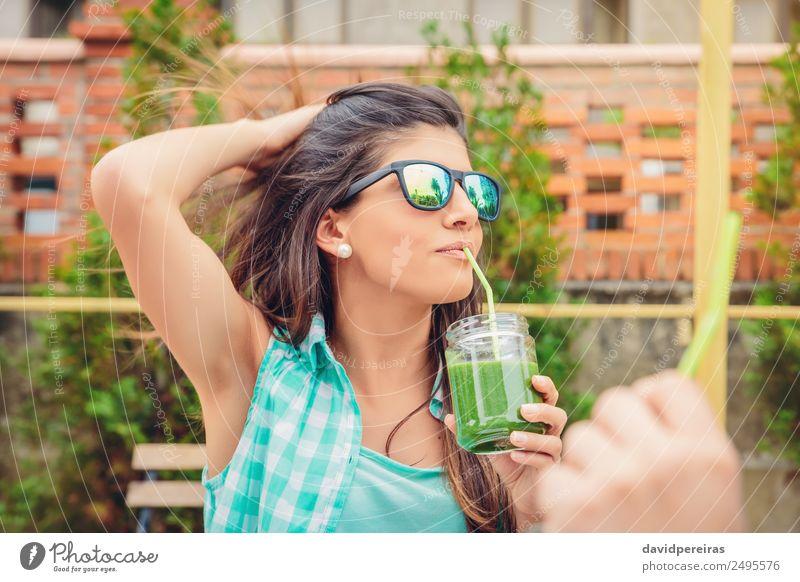 Frau mit Sonnenbrille, die im Freien grünen Gemüse-Smoothie trinkt. Frucht Ernährung Diät Getränk Saft Lifestyle Glück schön Sommer Garten Mensch Erwachsene