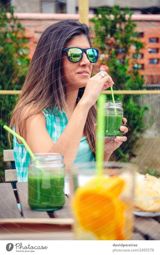 Frau mit Sonnenbrille, die im Freien grünen Gemüse-Smoothie trinkt. Frucht Ernährung Diät Getränk Saft Lifestyle Glück schön Sommer Mensch Erwachsene Natur