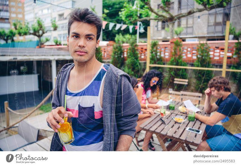 Junger Mann, der im Freien einen mit Wasser angereicherten Cocktail trinkt. Frucht Getränk Saft Lifestyle Freude Glück Freizeit & Hobby Sommer Garten Tisch