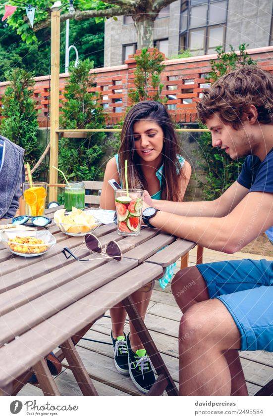 Junges glückliches Paar, das im Sommer im Freien ein Smartphone sucht. Gemüse Frucht Getränk Lifestyle Freude Glück Freizeit & Hobby Garten Tisch Telefon PDA