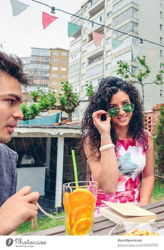 Lächelnde junge Frau schaut auf die Kamera über der Sonnenbrille. Frucht Getränk Tee Lifestyle Freude Glück Gesicht Freizeit & Hobby Sommer Tisch Mensch