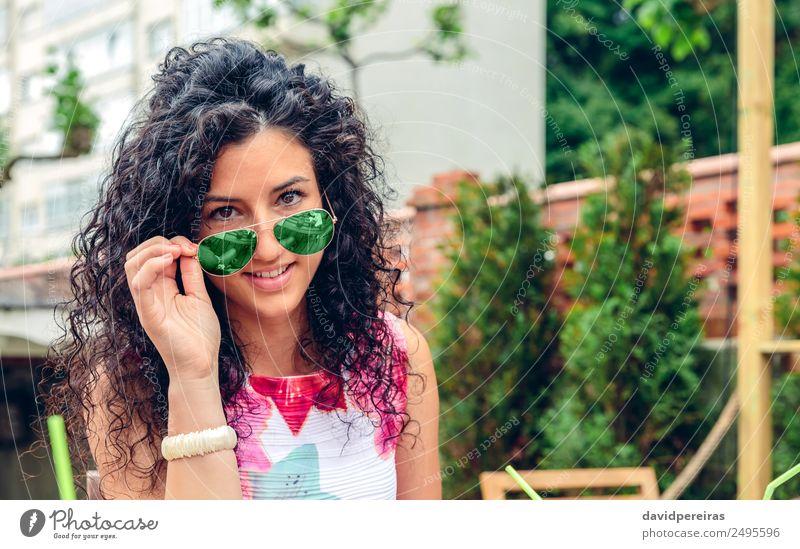 Lächelnde junge Frau schaut auf die Kamera über der Sonnenbrille. Lifestyle Freude Glück schön Gesicht Erholung Freizeit & Hobby Sommer Mensch Erwachsene Baum
