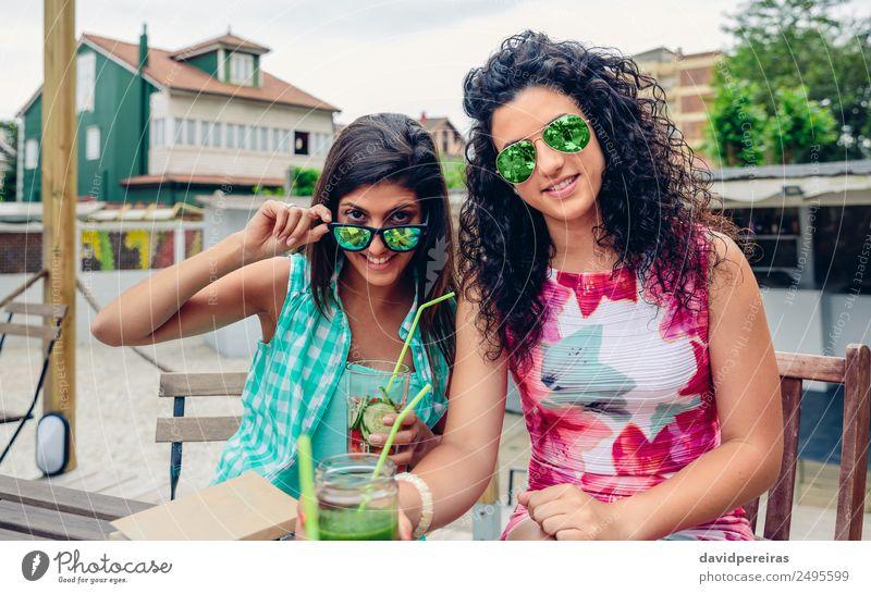 Zwei Frauen mit Sonnenbrille und Getränken, die auf die Kamera schauen. Gemüse Frucht Saft Lifestyle Freude Glück Freizeit & Hobby Sommer Mensch Erwachsene