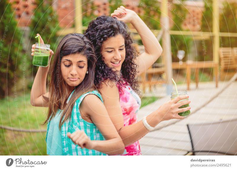 Junge Frauenpaar mit gesunden Getränken, das im Freien tanzt. Gemüse Frucht Alkohol Lifestyle Freude Glück schön Freizeit & Hobby Ferien & Urlaub & Reisen