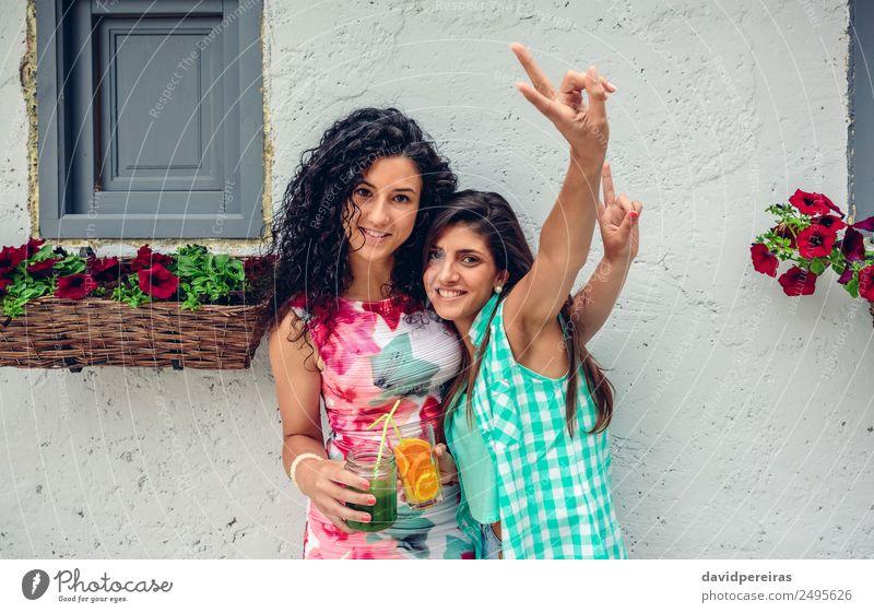Zwei Frauen mit Getränken, die Siegeszeichen machen. Gemüse Frucht Saft Lifestyle Freude Glück Freizeit & Hobby Sommer Erfolg Mensch Erwachsene Freundschaft