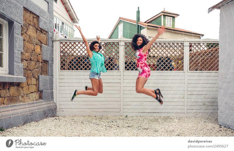 Glückliche Frauen springen vor dem Gartenzaun. Lifestyle Freude Freizeit & Hobby Sommer Mensch Erwachsene Freundschaft Arme brünett Holz genießen Lächeln lachen