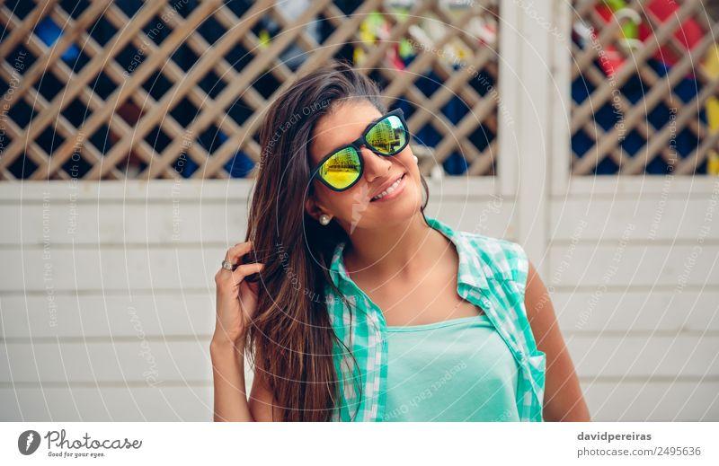Frau mit Sonnenbrille schaut auf die Kamera über dem Gartenzaun. Lifestyle Freude Glück schön Gesicht Freizeit & Hobby Sommer Spiegel Mensch Erwachsene Finger