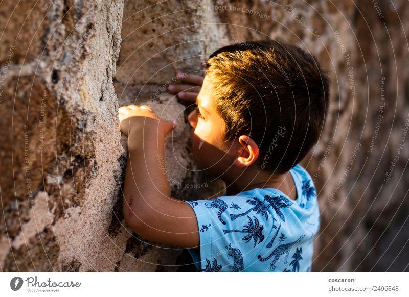 Kleiner Junge schaut durch die Mauer einer Burg. Gesicht Spielen Kind Mensch Mann Erwachsene Kindheit Gras Felsen Gipfel Dorf Kirche Burg oder Schloss Ruine