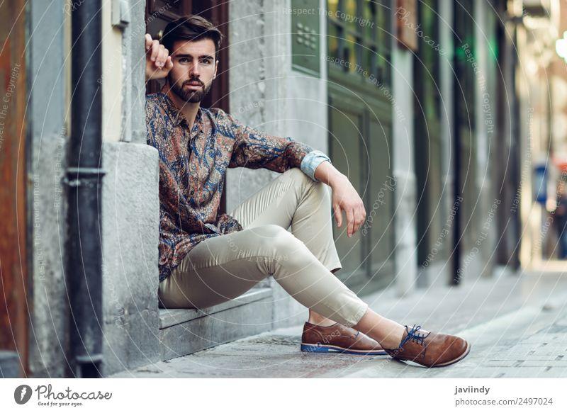 Junger bärtiger Mann, der in einer städtischen Stufe sitzt. Lifestyle Stil schön Haare & Frisuren Mensch maskulin Junger Mann Jugendliche Erwachsene 1