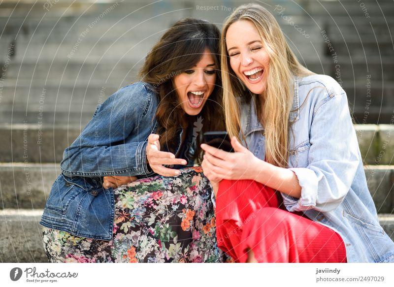 Zwei lachende Frauen, die auf ihr Smartphone schauen. Lifestyle kaufen Freude Glück schön Telefon PDA Technik & Technologie Mensch feminin Junge Frau