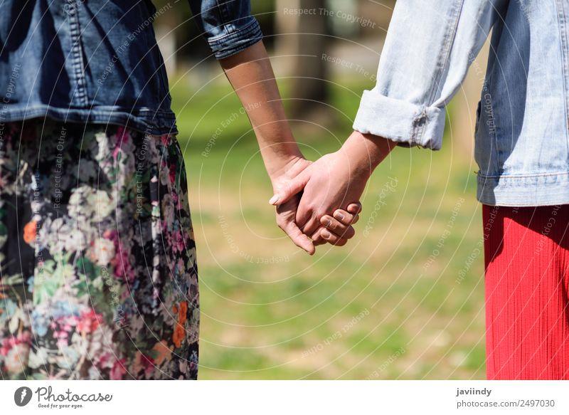 Zwei junge Frauen beim Gehen, die ihre Hände im Freien halten. Lifestyle Freude Glück schön Mensch feminin Junge Frau Jugendliche Erwachsene Freundschaft Paar