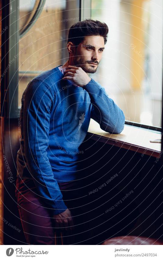 Junger Mann mit blauem Pullover und verlorenem Look in einem modernen Pub. Lifestyle Stil schön Haare & Frisuren Mensch maskulin Jugendliche Erwachsene 1