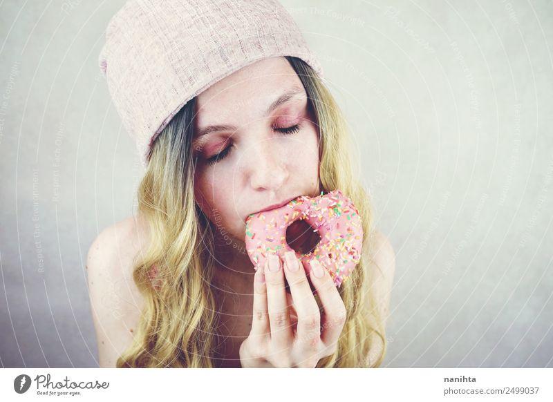 Junge Frau beim Essen eines rosa Donuts Lebensmittel Süßwaren Krapfen Fastfood Lifestyle Stil Design Freude schön Haare & Frisuren Mensch feminin Jugendliche