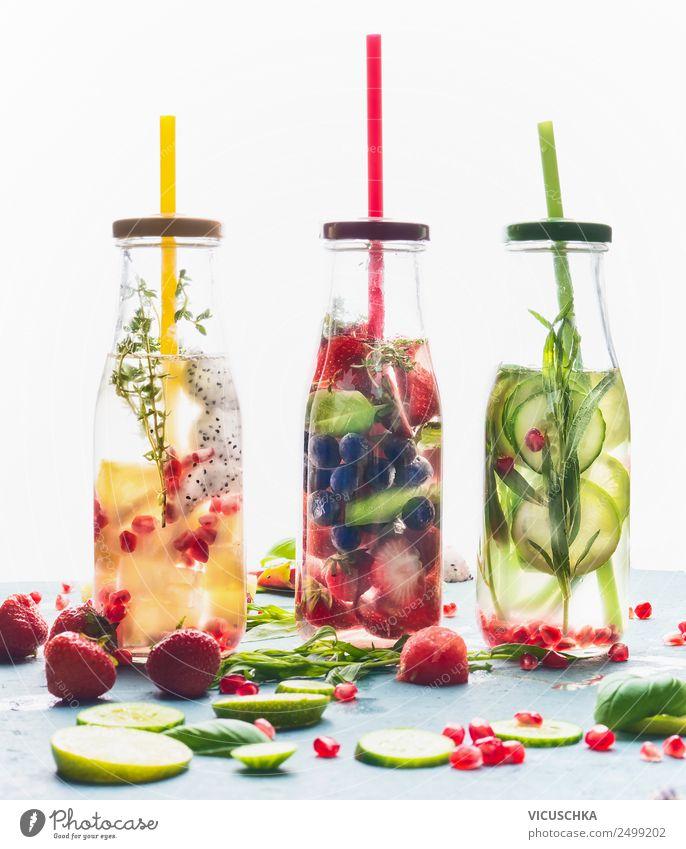 Aufgegossenes Wasser in Flaschen mit Trinkhalm und Zutaten auf weißem Hintergrund, Vorderansicht. Wasser, das mit Früchten, Beeren und Kräutern gewürzt ist. Sommergetränke. Gesunde und saubere Entgiftungsgetränke.