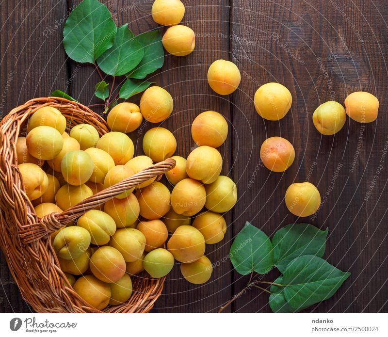 Reife gelbe Aprikosen Frucht Ernährung Vegetarische Ernährung Diät Tisch Natur Blatt Holz frisch lecker natürlich saftig braun Farbe Korb Ackerbau Hintergrund