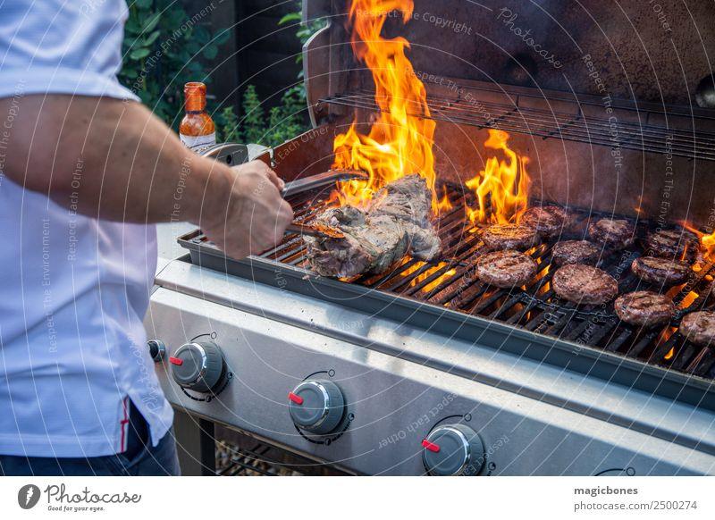 Mann beim Kochen auf dem Grill Fleisch Kräuter & Gewürze Sommer Garten heiß lecker grillen Hinterhof Barbecue Rindfleischburger Beefburger Brand lodernd Burger
