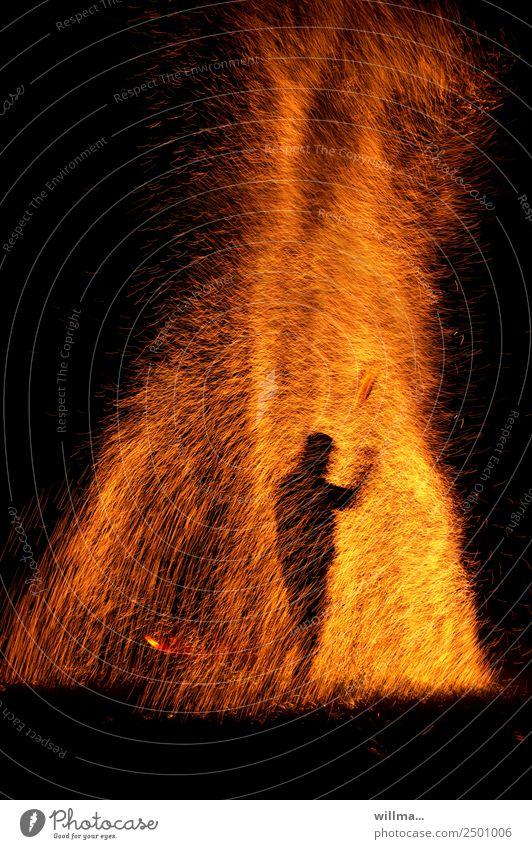 Mensch steht im Funkenregen Feuer Silhouette heiß bedrohlich brennen Brand Flamme gefährlich Brandstiftung Textfreiraum unten Nacht Urelemente