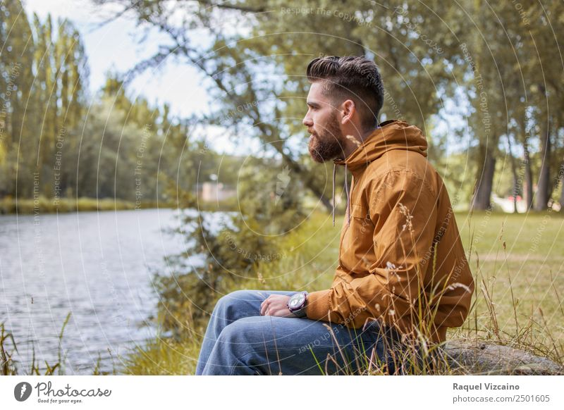 Mann sitzt am Fluss im Herbst. Lifestyle Mensch maskulin Junger Mann Jugendliche Körper 1 18-30 Jahre Erwachsene Natur Landschaft Wasser Baum Feld Flussufer