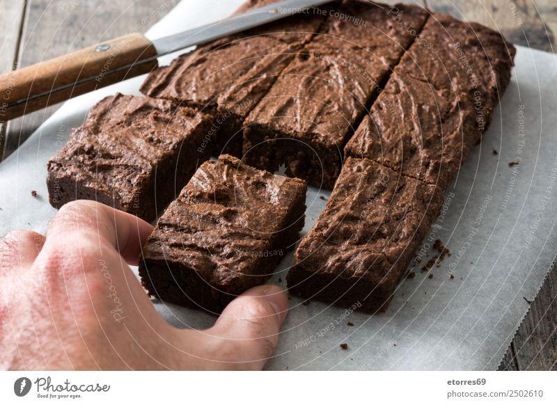 Hand fängt eine Schokoladenbrownie-Portion ein. Lebensmittel Dessert Süßwaren Ernährung Bioprodukte Vegetarische Ernährung Diät Messer Holz schwarz Kuchen