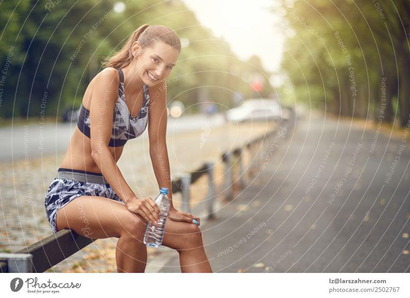 Glückliche Frau, die eine Pause vom Joggen macht. trinken Lifestyle Sommer Sport Erwachsene 1 Mensch 18-30 Jahre Jugendliche Wärme Straße Fitness Lächeln Erfolg
