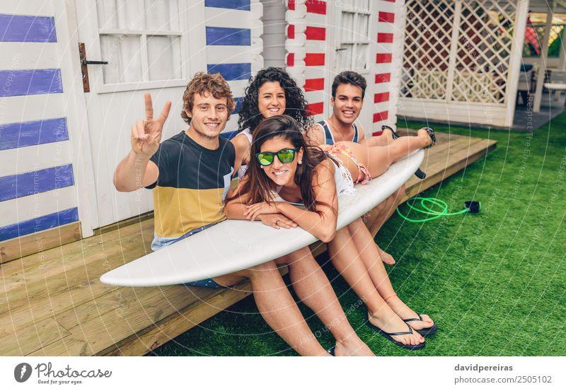 Junge Freunde halten Frau auf dem Surfbrett fest. Lifestyle Freude Glück schön Freizeit & Hobby Ferien & Urlaub & Reisen Sommer Strand Meer Garten Sport