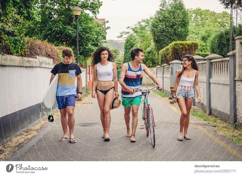 Glückliche junge Menschen, die am Sommertag die Straße entlang gehen. Lifestyle Freude Erholung Freizeit & Hobby Ferien & Urlaub & Reisen Sport Frau Erwachsene