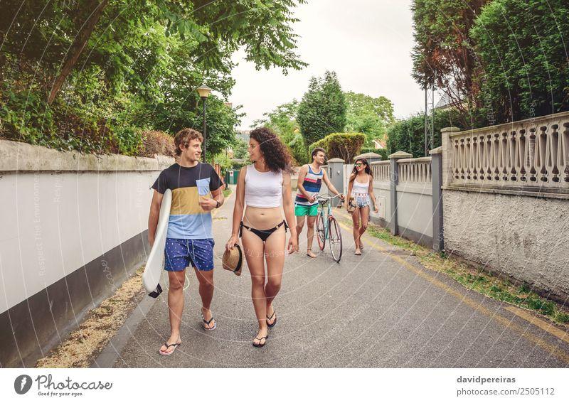 Glückliche junge Menschen, die am Sommertag die Straße entlang gehen. Lifestyle Freude Freizeit & Hobby Ferien & Urlaub & Reisen Sport Frau Erwachsene Mann