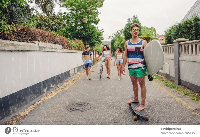 Junger Mann fährt auf dem Skate und hält Surfbrett. Lifestyle Freude Glück Freizeit & Hobby Sommer Strand Sport Frau Erwachsene Freundschaft Jugendliche