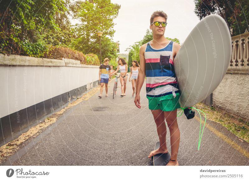 Junger Mann fährt auf dem Skate und hält Surfbrett. Lifestyle Freude Glück schön Erholung Freizeit & Hobby Ferien & Urlaub & Reisen Sommer Strand Sport Frau