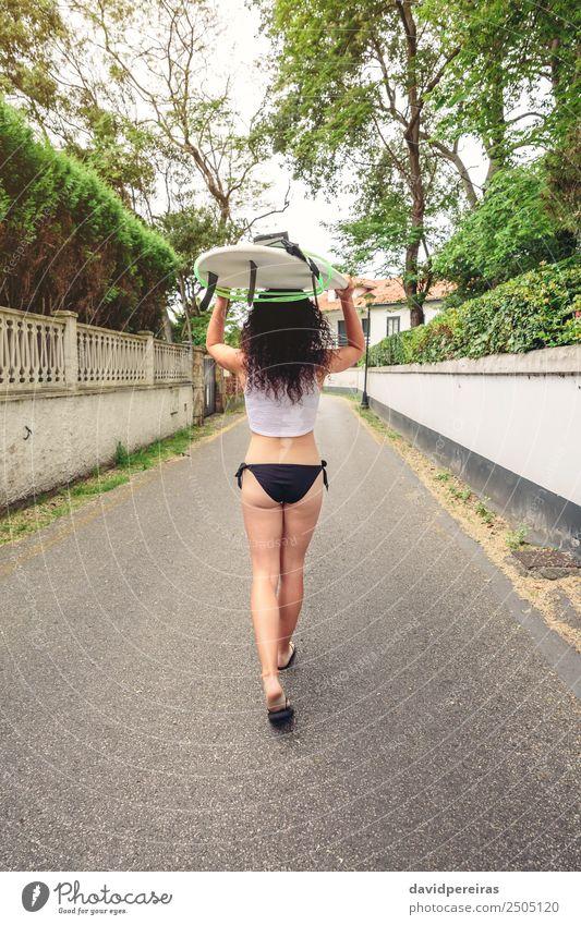 Brünettes Mädchen hält Surfbrett über Kopf und geht spazieren. Lifestyle Freude Glück schön Freizeit & Hobby Ferien & Urlaub & Reisen Sommer Strand Meer Sport