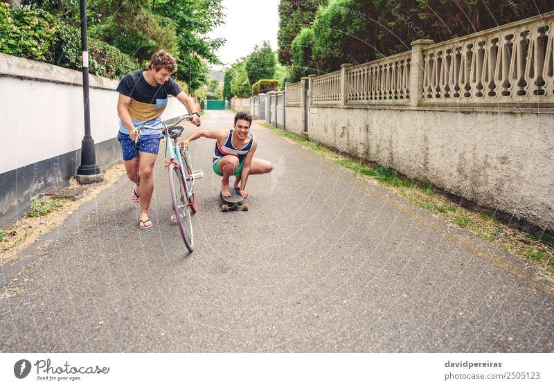 Zwei Männer, die Spaß am Fahren mit Fahrrad und Skateboard haben. Lifestyle Freude Glück Erholung Freizeit & Hobby Ferien & Urlaub & Reisen Sommer Sport Mann